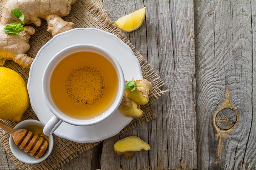 Ginger tea and ingredients on rustic wood background, copy space